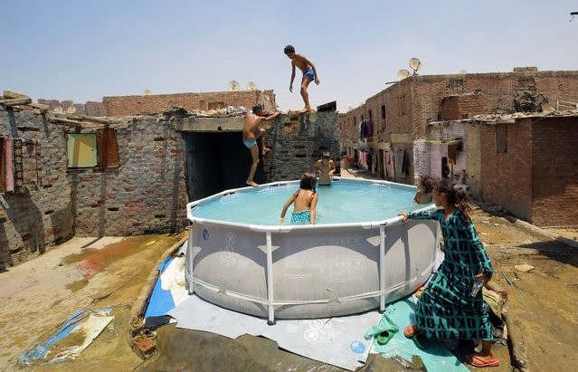Egyptian children cool off in a makeshift swimming pool at Manshiyat Naser slum area, Cairo, Egypt, 24 July 2019. Temperatures have been higher than average in Egypt, reaching 40 degrees in Cairo and 46 in southern Egypt. (Photo by Khaled Elfiqi/EPA/EFE)