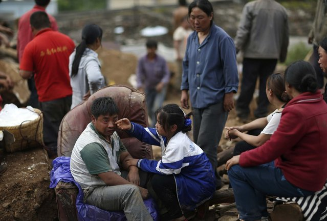 Liu Jiali (front L) cries as his daughter (C) wipes his tear after an earthquake killed Liu's wife and two other children in Longtoushan township of Ludian county, Yunnan province August 4, 2014. A magnitude 6.3 earthquake struck southwestern China on Sunday, killing at least 398 people in a remote area of Yunnan province, and causing thousands of buildings, including a school, to collapse. (Photo by Wong Campion/Reuters)
