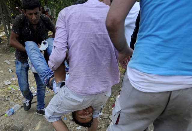 People carry their friend who collapsed at the border line dividing Macedonia and Greece August 21, 2015. (Photo by Ognen Teofilovski/Reuters)