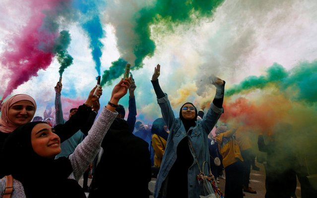Iraqi women wave colored smoke candles during the festival of colors, in the holy Shi'ite city of Najaf, Iraq on January 15, 2020. (Photo by Alaa al-Marjani/Reuters)