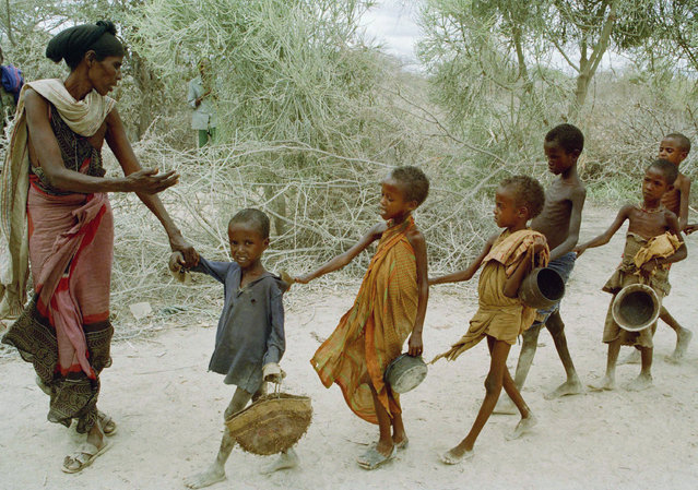 A woman leads children to a food kitchen after they had been waiting since early morning to be fed in Berdale, southwest Somalia, August 25, 1992. On this day, only half of the starving children had been fed when the food ran out. The International Committee of the Red Cross urged increased coordination of relief efforts to the starving country. (Photo by Greg Marinovich/AP Photo)