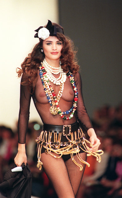 A model presents a transparent body suit worn under a chain mini-skirt by German designer Karl Lagerfeld of Chanel during the 91/92 Fall/Winter ready-to-wear collections in Paris, 18 March 1991. (Photo by Pierre Guillaud/AFP Photo)