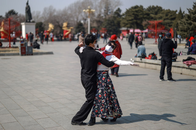 This photo taken on March 22, 2020 shows a man and a woman wearing face masks dancing at a park in Shenyang in China's northeastern Liaoning province. China reported no new local cases of the deadly coronavirus on March 23, but confirmed another 39 infections brought in from overseas. (Photo by AFP Photo/China Stringer Network)