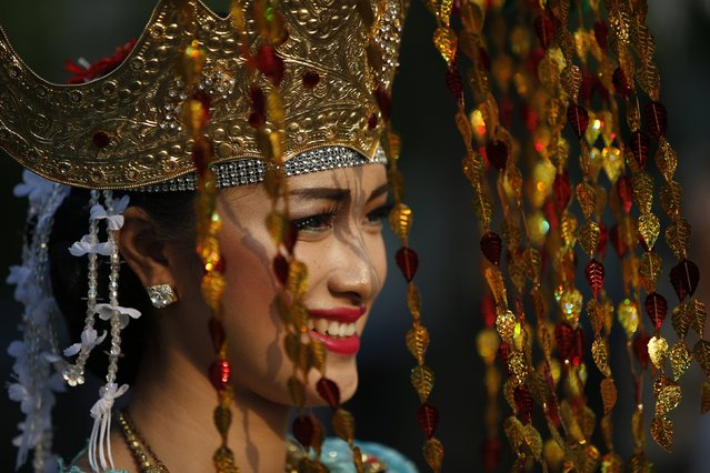 An Indonesian dancer smiles while waiting for the start of a cultural parade marking the country's 69th Independence Day celebration in Jakarta August 18, 2014. (Photo by Darren Whiteside/Reuters)