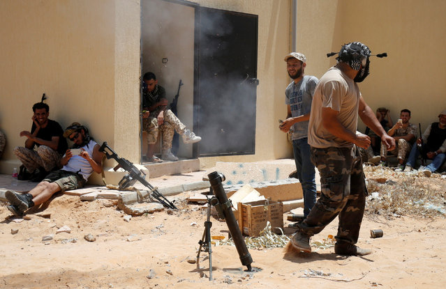 A fighter of Libyan forces allied with the U.N.-backed government fires a mortar during a battle with IS fighters in Sirte, Libya, July 21, 2016. (Photo by Goran Tomasevic/Reuters)