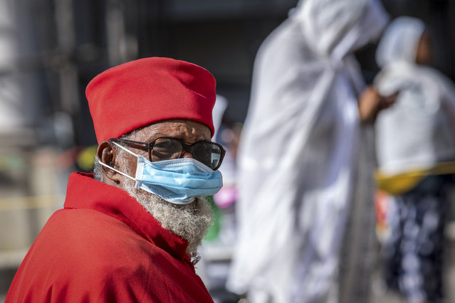 A priest wears a mask to limit the risk of infection by the new coronavirus, as he attends a Sunday morning mass at the Bole Medhane Alem Ethiopian Orthodox Cathedral in Addis Ababa, Ethiopia Sunday, April 5, 2020. (Photo by Mulugeta Ayene/AP Photo)