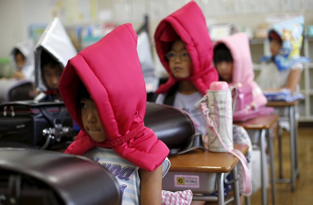 School children wearing padded hoods to protect them from falling debris, prepare to evacuate during an earthquake simulation exercise at an elementary school in Tokyo September 1, 2015. (Photo by Toru Hanai/Reuters)