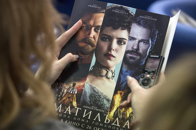 """In this Tuesday, June 13, 2017 file photo, a woman holds an official poster of Russian film director Alexei Uchitel's film """"Matilda"""" at a news conference in Moscow, Russia. Russian police has detained four people suspected of an arson attack linked to a controversial movie about the Russian last czar's love affair, it was announced on Thursday, September 21, 2017. The movie, """"Matilda"""", which is set to be released in October, has sparked harsh criticism from hard-line nationalists and some Orthodox believers in Russia. (Photo by Pavel Golovkin/AP Photo)"""