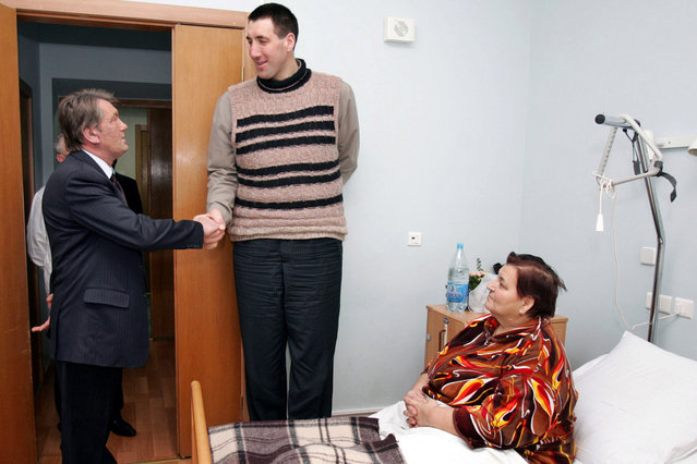 Ukrainian President Viktor Yushchenko (L) shakes hands with Leonid Stadnyk, who stands 2.53 metres (8 feet 3 inches) tall, during a visit to Stadnyk's mother (R) in hospital in Kiev January 18, 2006. Stadnyk, who may possibly be the world's tallest man, brought his elderly mother from their village in western Ukraine for treatment to a Kiev hospital, where he met the president. (Photo by Mykhaylo Markiv/Reuters)