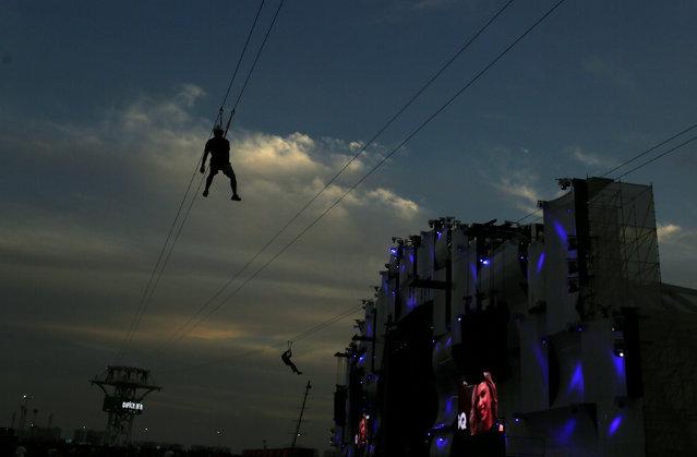 Rock fans ride a zipline during the Rock in Rio Music Festival in Rio de Janeiro, Brazil September 22, 2017. (Photo by Pilar Olivares/Reuters)