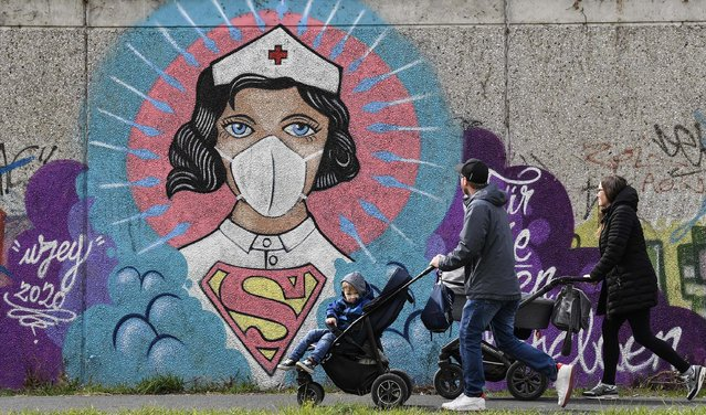 """People look at a coronavirus graffiti by street artist """"Uzey"""" showing a nurse as Superwoman on a wall during a walk in Hamm, Germany, on Easter Monday, April 13, 2020. (Photo by Martin Meissner/AP Photo)"""