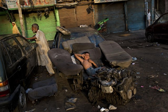A homeless Indian child stretches as he wakes up from his bed made of car seat covers in New Delhi, India, Tuesday, August 26, 2014. Some 800 million people in the country live in poverty, many of them migrating to big cities in search of a livelihood and often ending up on the streets. (Photo by Bernat Armangue/AP Photo)