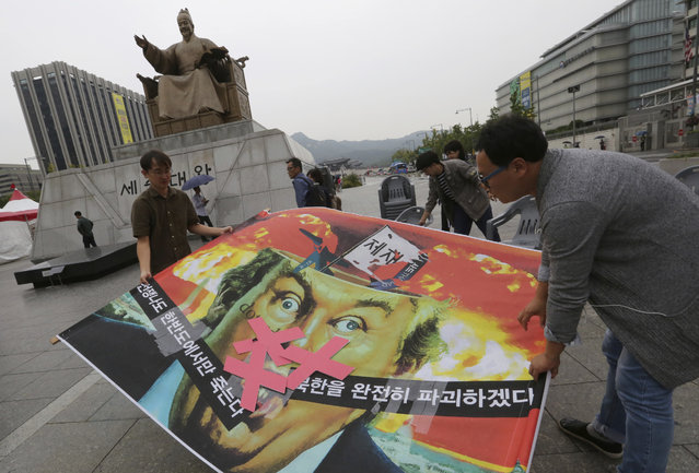 """South Korean protesters carry a caricature of U.S. President Donald Trump during a rally to denounce the United States' policy against North Korea, near U.S. Embassy in Seoul, South Korea, Wednesday, September 27, 2017. North Korea's top diplomat said Monday that a weekend tweet by Trump was a """"declaration of war"""" and North Korea has the right to retaliate by shooting down U.S. bombers, even in international airspace. The caricature reads: """"North Korea is destroyed"""". (Photo by Ahn Young-joon/AP Photo)"""