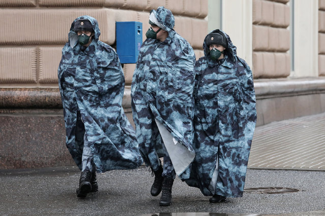 Russian law enforcement officers wearing raincoats and protective masks patrol the streets amid the coronavirus disease (COVID-19) outbreak in Moscow, Russia on April 14, 2020. (Photo by Sofya Sandurskaya/Moscow News Agency/Handout via Reuters)