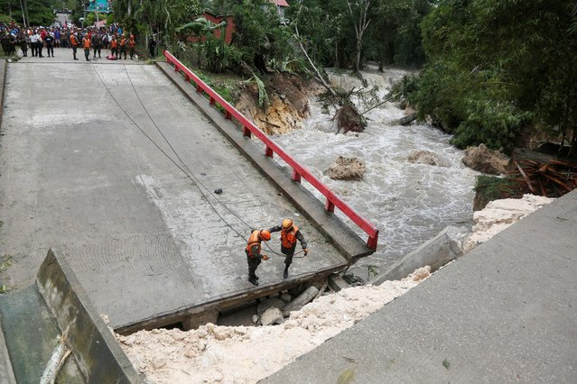 Members of Guatemalan emergency commission (CONRED) stand at a bridge that collapsed after heavy rains brought by Hurricane Earl at Menchor de Mencos, Guatemala, August 4, 2016. (Photo by Luis Echeverria/Reuters)