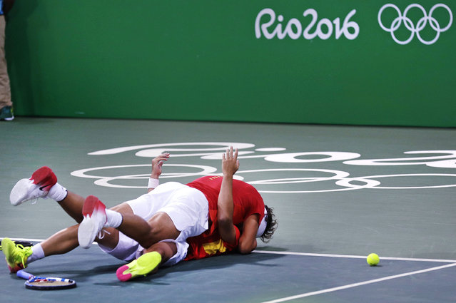 Rafael Nadal, of Spain, top, embraces partner Marc Lopez as they celebrate after defeating Canada in their men's doubles match at the 2016 Summer Olympics in Rio de Janeiro, Brazil, Thursday, August 11, 2016. (Photo by Charles Krupa/AP Photo)