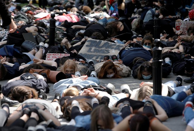 Demonstrators lie on the ground during a protest over police brutality towards African-Americans in the United States, after the death of George Floyd in Minneapolis police custody, in front of the U.S. embassy in Warsaw, Poland, June 4, 2020. (Photo by Kacper Pempel/Reuters)