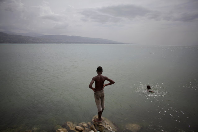A boy stands as another one cools off at a wharf in Port-au-Prince, Haiti, July 30, 2016. (Photo by Andres Martinez Casares/Reuters)