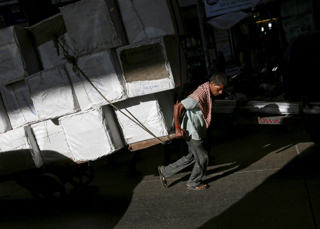 A porter pulls a handcart loaded with goods at a market in Mumbai, India, September 8, 2015. (Photo by Danish Siddiqui/Reuters)