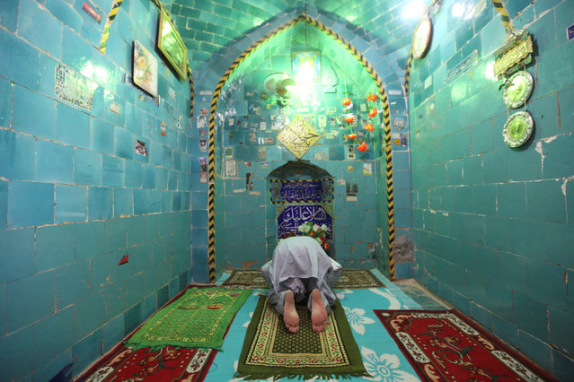 """A man prays inside the shrine of Imam Mahdi at the Wadi al-Salam cemetery, Arabic for """"Peace Valley"""", in Najaf, south of Baghdad, Iraq, August 1, 2016. (Photo by Alaa Al-Marjani/Reuters)"""