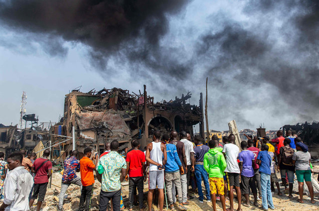 People gather at the scene of a gas explosion near destroyed buildings in Lagos on March 15, 2020. A gas explosion in Nigeria's commercial capital Lagos killed at least 15 people, injured many more and destroyed around 50 buildings on March 15, 2020. (Photo by Benson Ibeabuchi/AFP Photo)