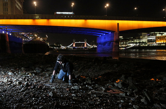A mudlark uses a torch to look for objects under London Bridge on the bank of the River Thames in London, Britain June 06, 2016. (Photo by Neil Hall/Reuters)