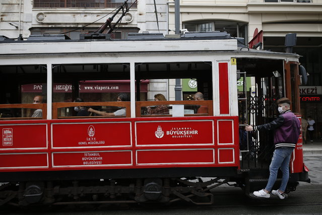 People, wearing protective masks against the spread of coronavirus, use the tram on Istiklal street, the main shopping street in Istanbul, Thursday, June 18, 2020. (Photo by Emrah Gurel/AP Photo)