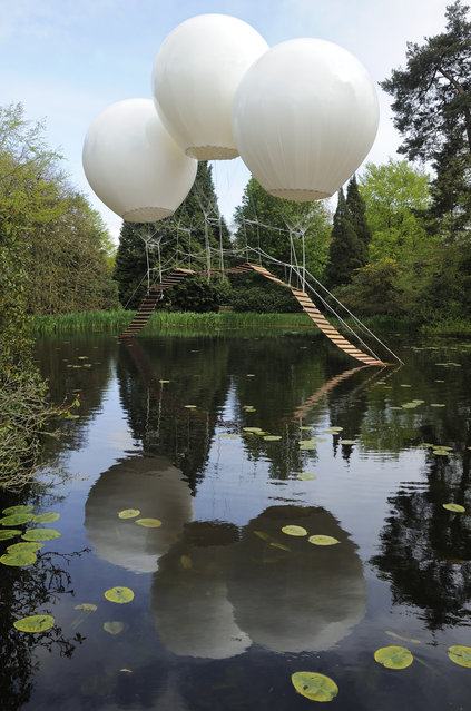 "French artist Olivier Grossetête used three enormous helium balloons to float a rope bridge over a lake in Tatton Park, a historic estate in north-west England. Though visitors weren't allowed to use the bridge, it would theoretically be strong enough to hold the weight of a person, according to Grossetête.""My artistic work tries to make alive the poetry and dreams within our everyday life,"" added Grossetête. (Photo by Thierry Bal)"