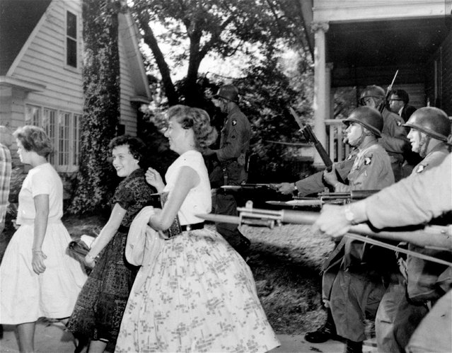 In this September 25, 1957, file photo, troopers of the 101st Airborne Division with fixed bayonets draw giggles from Central High School students in Little Rock, Ark. Federal forces were employed to enforce integration in the face of racial tension at the school. The city is marking the 50th anniversary of Central High School's integration in September 2007 with a series of events culminating in a ceremony featuring former president Clinton and the Little Rock Nine. (Photo by AP Photo)