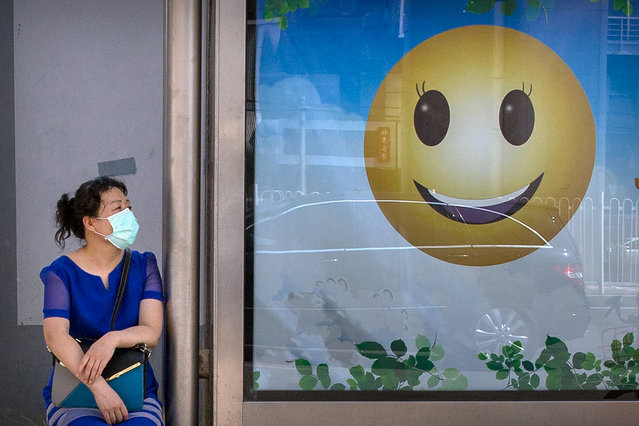 A woman wearing a face mask to protect against the new coronavirus waits at a bus stop in Beijing, Tuesday, July 14, 2020. Health experts are warning that outbreaks brought under control with shutdowns and other forms of social distancing are likely to flare again as precautions are relaxed.(Photo by Mark Schiefelbein/AP Photo)