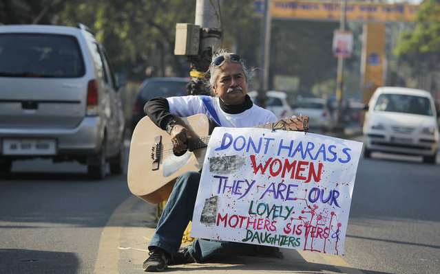 Indian music director and social activist Kishor Giri sits on a road median, showing his protest against the brutal gang-rape of a woman on a moving bus last week in New Delhi, in Gauhati, India, on December 25, 2012. (Photo by Anupam Nath/AP Photo)