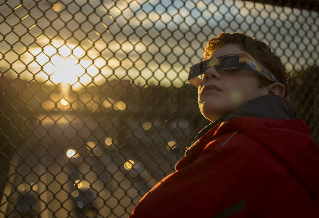 In this handout photo provided by NASA, Alex Frye, 12, uses special viewing glasses to look at a partial solar eclipse from a highway overpass October 23, 2014, in Arlington, Virginia. A partial eclipse occurs when the moon covers a portion of the sun as seen from the Earth. (Photo by Bill Ingalls/NASA via Getty Images)