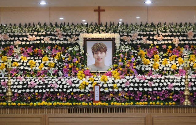 """The portrait of Kim Jong-Hyun, a 27-year-old lead singer of the massively popular K-pop boyband SHINee, is seen on a mourning altar at a hospital in Seoul on December 19, 2017. The top K-pop star bemoaned feeling """"broken from inside"""" and """"engulfed"""" by depression in a suicide note, it emerged on December 19, as his death sent shockwaves across K-pop fans worldwide. (Photo by Choi Hyuk/AFP Photo)"""