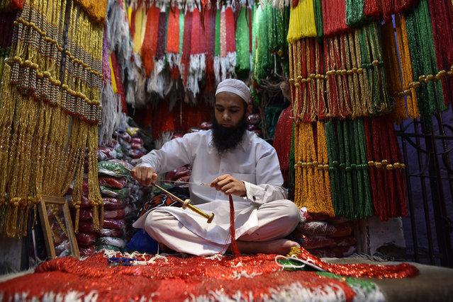 A shop vendor weaving glass beads as the month of Shrawan begins in Kathmandu, Nepal on  July 16, 2020.(Photo by Narayan Maharjan/NurPhoto via Getty Images)
