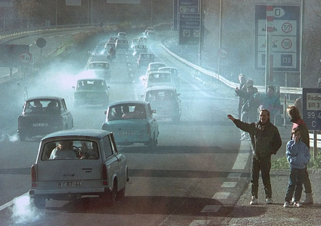 East German Trabant cars make their way past East Germans who have crossed the former border checkpoint Rudolphstein in Bavaria on motorway A9 after the opening of the East German border was announced, November 11, 1989. (Photo by Reuters)