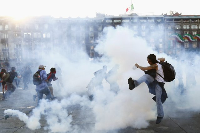 A protester kicks a tear gas canister during clashes with riot police at a march marking the 47th anniversary of the 1968 Tlatelolco square massacre at Zocalo square in Mexico City, October 2, 2015. Thousands took part in the march to mark the 47th anniversary of the student massacre at which dozens, maybe hundreds, of protesters were gunned down by the army in a brutal repression of the student movement. (Photo by Edgard Garrido/Reuters)