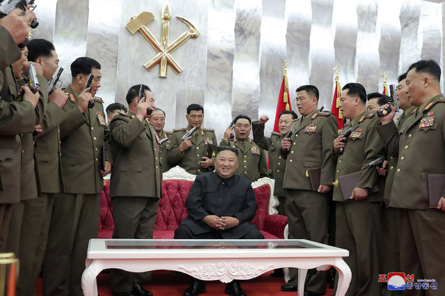 """In this Sunday, July 26, 2020, photo released by the North Korean government, North Korean leader Kim Jong Un, sitting, is surrounded by senior military officials holding """"Paektusan"""" commemorative pistols they received from Kim during a ceremony in Pyongyang, North Korea. Independent journalists were not given access to cover the event depicted in this image distributed by the North Korean government. The content of this image is as provided and cannot be independently verified. Korean language watermark on image as provided by source reads: """"KCNA"""" which is the abbreviation for Korean Central News Agency. (Photo by Korean Central News Agency/Korea News Service via AP Photo)"""