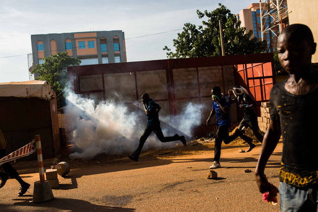 Protestors on the rampage near the  parliament building in Burkina Faso as people protest  against their longtime president Blaise Compaore  who seeks another term in Ouagadougou, Burkina Faso, Thursday, October 30, 2014. (Photo by Theo Renaut/AP Photo)
