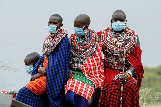 Masai women dressed in traditional clothes wear surgical masks as they wait for a ceremony marking World Elephant Day in the Amboseli National Park, Kenya, August 12, 2020. (Photo by Baz Ratner/Reuters)