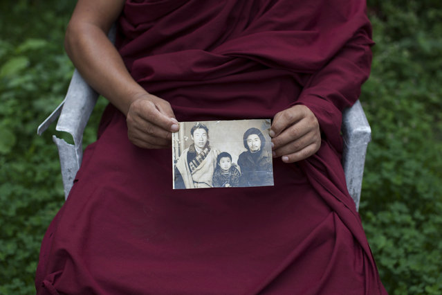 In this Saturday, September 27, 2014 photo, Tibetan monk Dorjee, 38, displays a photograph of his father, left, and himself, center, taken in Tibet, in Dharamsala, India. Dorjee said he held back his tears when he spoke with his parents on the phone after a separation period of 27 years. He exchanged a few words with his father but said his mother fainted on hearing his voice. (Photo by Tsering Topgyal/AP Photo)
