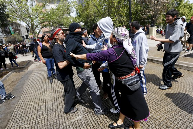 Mapuche Indian activists argue amongst themselves during a protest march by Mapuche Indian activists against Columbus Day in downtown Santiago, Chile, October 12, 2015. (Photo by Ivan Alvarado/Reuters)
