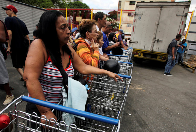 People stand in line as they wait to buy staple items and basic food outside of a supermarket in El Paraiso neighborhood in Caracas, Venezuela September 9, 2016. (Photo by Henry Romero/Reuters)