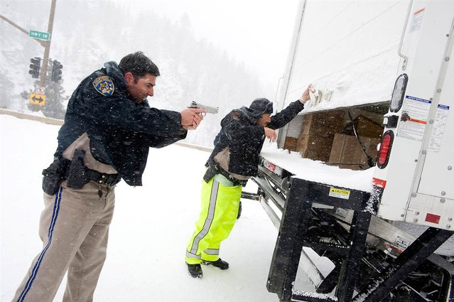 Two California Highway Patrol officers check the cargo of a truck leaving the Big Bear Lake area on February 8, during a manhunt for Christopher Dorner, who was suspected of killing three people, including a Corona, Calif., police officer. Dorner later killed a deputy and wounded another before dying in a fire that consumed the cabin he was holed up in. (Photo by Michael Goulding/The Orange County Register via Zuma Press)