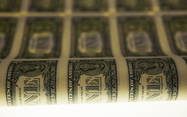 A sheet of one dollar bills is seen on a light table during production at the Bureau of Engraving and Printing in Washington November 14, 2014. (Photo by Gary Cameron/Reuters)