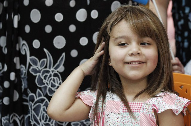 Alexandra Munoz, 5, who lost her hair due to chemotherapy for a brain tumor, plays with her new natural hair wig after it was fitted to her for the first time in the cancer ward of the Luis Calvo Mackenna Hospital in Santiago, October 23, 2014. (Photo by Rodrigo Garrido/Reuters)