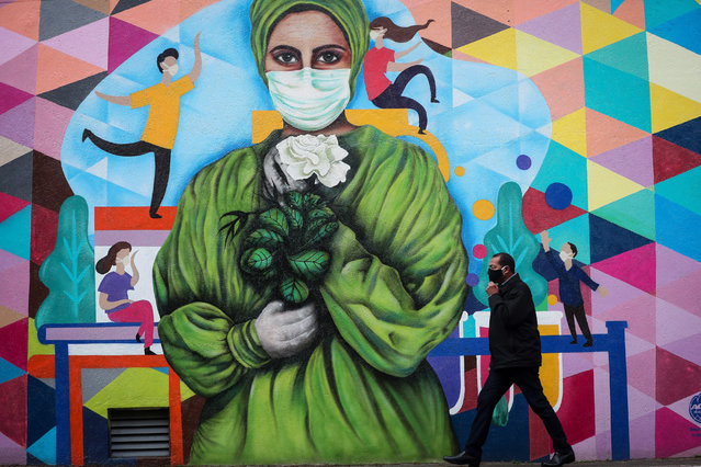 People walk past a mural honoring health workers at Hospital das Clinicas, in Sao Paulo, Brazil, 20 August 2020. The creators of the murals, Waldir Grisolia and Roberto Alves, had the participation of health professionals in the realization of the graffiti. (Photo by Fernando Bizerra/EPA/EFE)