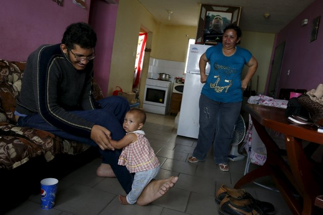 Jeison Rodriguez (L), 19, the living person with the largest feet in the world, holds his niece Osmariel with the help of his foot at his house in Maracay, Venezuela, October 14, 2015. (Photo by Carlos Garcia Rawlins/Reuters)