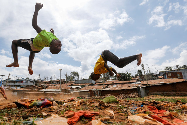 Children flip through the air as they play on dumped plastic materials amid the spread of the coronavirus disease (COVID-19) within Kibera slums in Nairobi, Kenya on June 7, 2020. (Photo by Thomas Mukoya/Reuters)