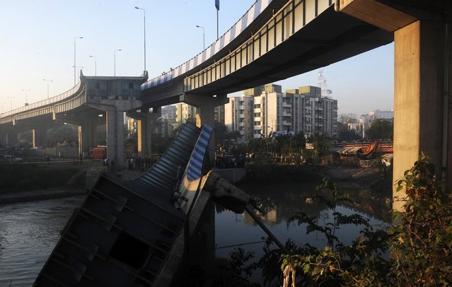 Indian onlookers stand near the collapsed portion of the flyover in Kolkata on March 3, 2013.  A huge portion of a flyover on the eastern side of the Indian metropolis collapsed leaving three persons injured, the flyover connects the airport with Eastern Metropolitan Bypass and the eastern and southern suburbs.   As the debris fell into a canal running below the flyover, it took down a truck the driver and two others were rescued from the canal by fire-brigade personnel and locals. (Photo by Dibyangshu Sarkar/AFP Photo)