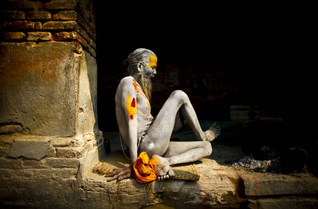 A Hindu Holy man, with ash smeared on his body, tries to stretch as he rests inside the premises of Pashupatinath Temple in Katmandu, Nepal, on March 4, 2013. Hindus across the world will be celebrating Mahashivratri, or Shiva's night festival on March 10, believed to be the day when Shiva got married. (Photo by Niranjan Shrestha/Associated Press)